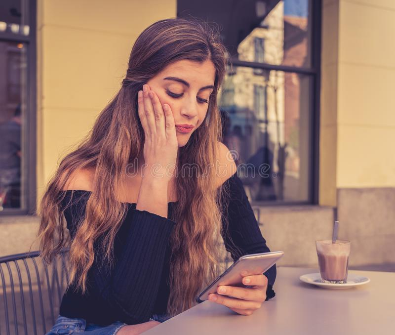 De aantrekkelijke jonge vrouwenzitting bored in een koffiewinkel gebruikend slim mobiel teleurgesteld telefoongevoel royalty-vrije stock afbeelding