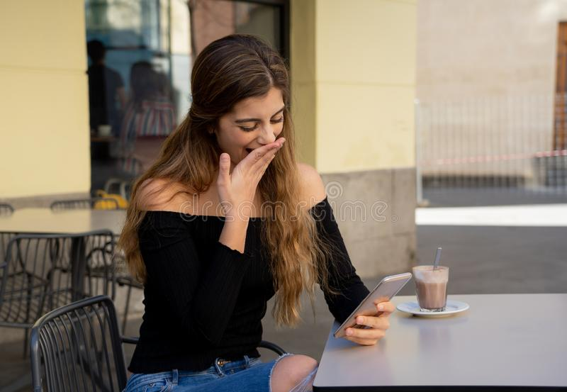 De aantrekkelijke jonge vrouwenzitting bored in een koffiewinkel gebruikend slim mobiel teleurgesteld telefoongevoel royalty-vrije stock afbeeldingen