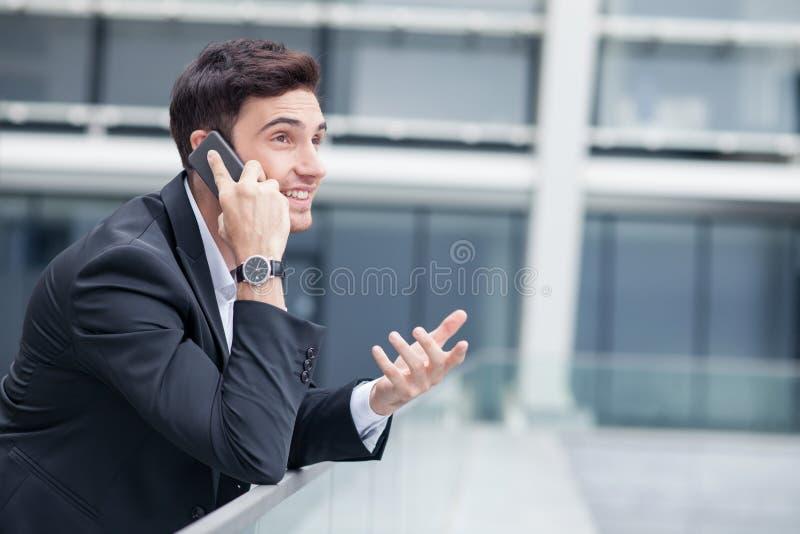 De aantrekkelijke jonge zakenman is mededeling over royalty-vrije stock afbeelding