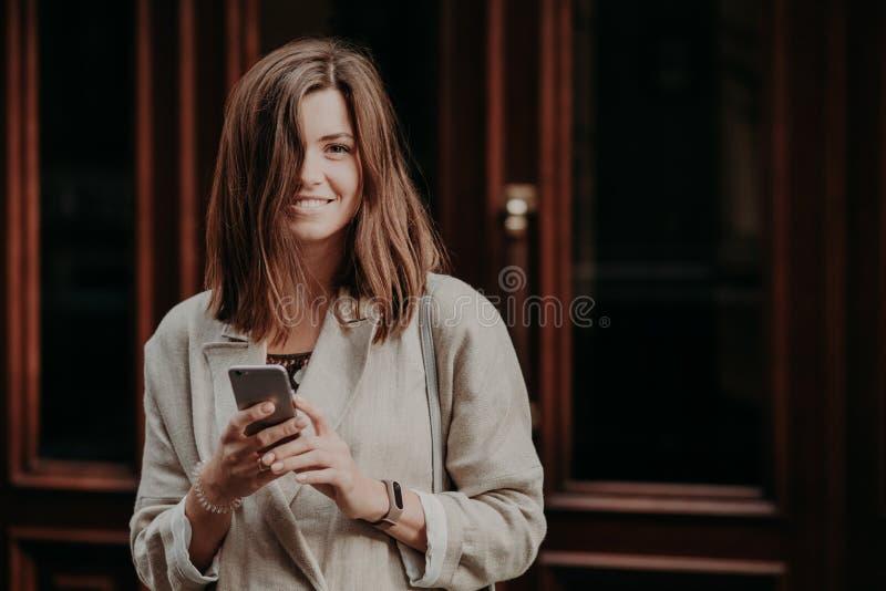 De aantrekkelijke jongelui die de vrouwelijke berichten van bloggerteksten glimlachen aan aanhangers, hebt recreatietijd, die in  royalty-vrije stock fotografie