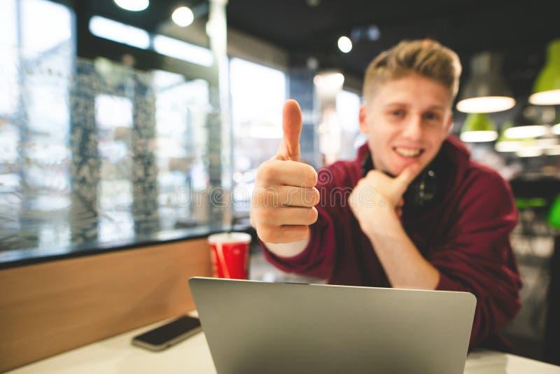 De aantrekkelijke kerel met laptop in de koffie toont duimen royalty-vrije stock afbeeldingen