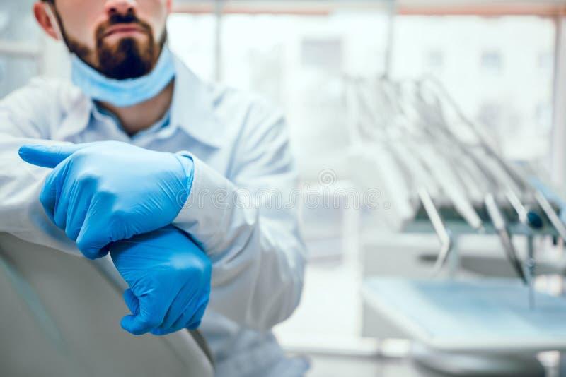 De aantrekkelijke knappe tandarts in beschermend gezichtsmasker, witte laboratoriumlaag zit op de stoel tandartsmateriaal op acht stock afbeelding
