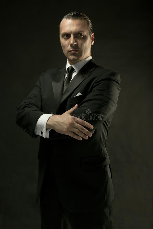 De aantrekkelijke man in zwart kostuum op donkere achtergrond stock foto