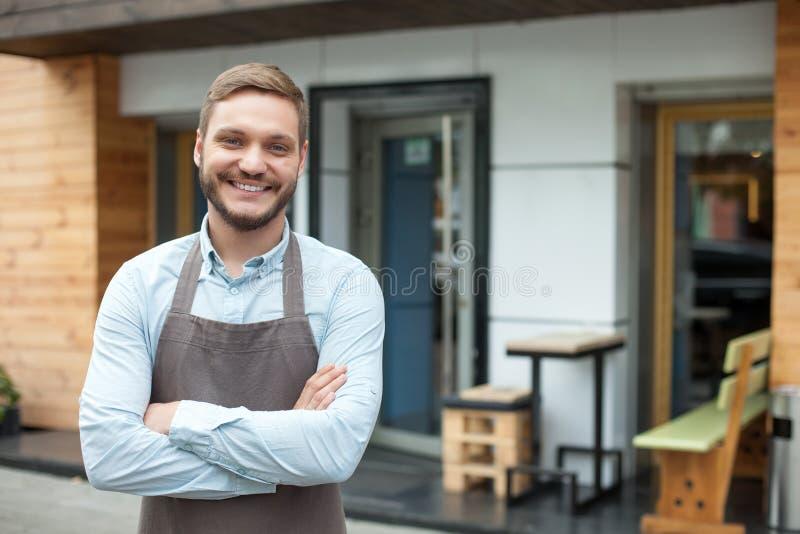 De aantrekkelijke mannelijke eigenaar van cafetaria wacht op stock fotografie