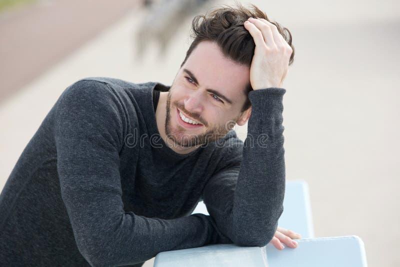 De aantrekkelijke mens die glimlachen met dient haar in stock foto's