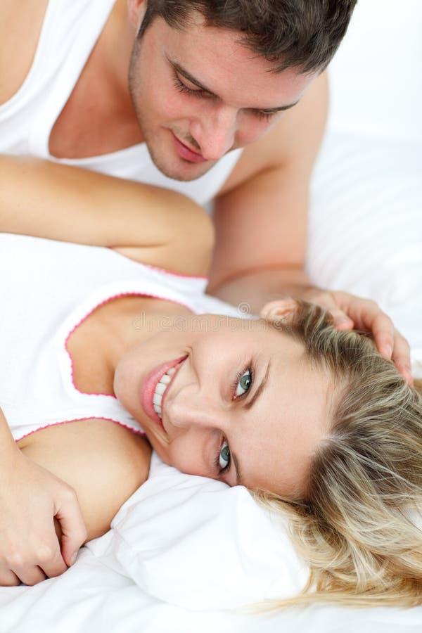 De aantrekkelijke mens die van hem bekijkt girlfrined in bed stock foto's
