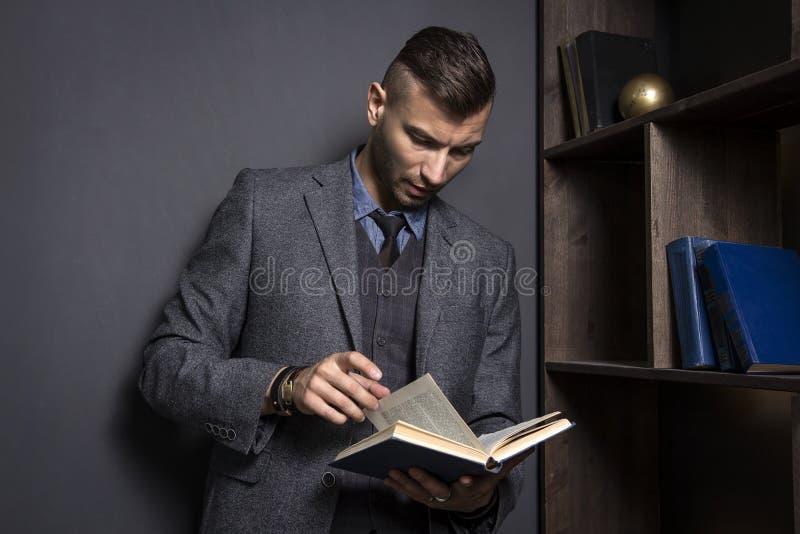 De aantrekkelijke mens in een pak leest een boek De advocaat houdt de folder in zijn bureau Lerende mens met boek royalty-vrije stock fotografie