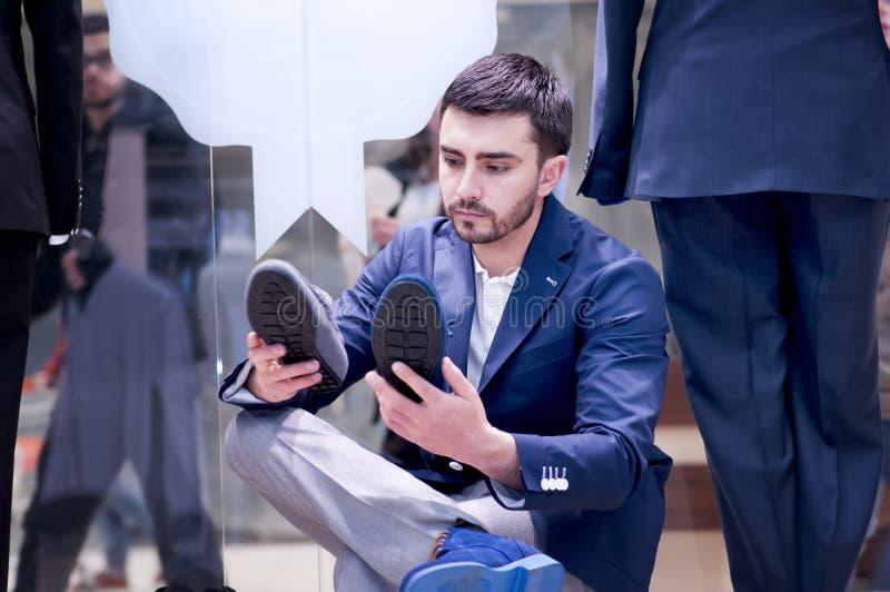 De aantrekkelijke mens kiest schoenen bij een winkel. stock foto's