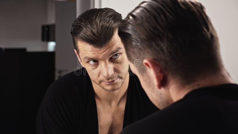De aantrekkelijke mens voor een spiegel in een zwart overhemd onderzoekt zich stock fotografie
