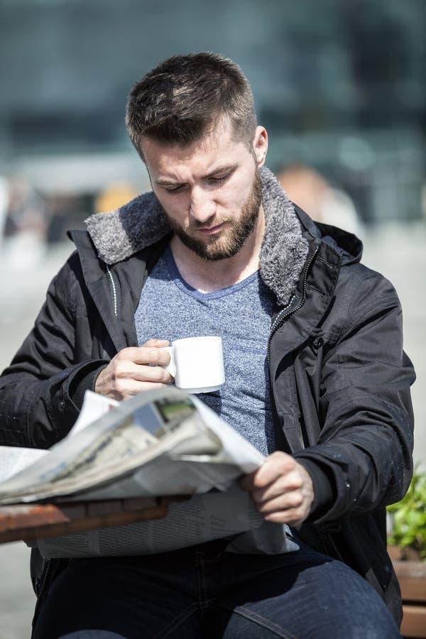 De aantrekkelijke mens zit in een koffiewinkel lezend het nieuwsdocument royalty-vrije stock fotografie