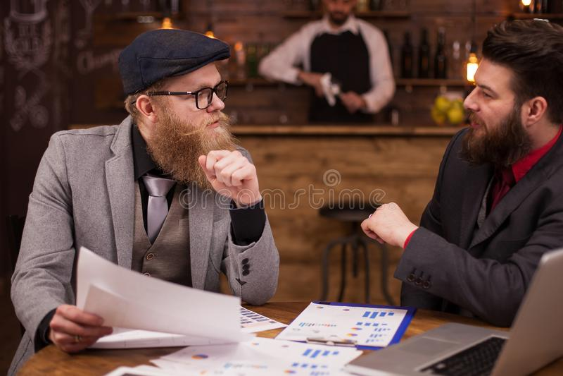 De aantrekkelijke mensen die met zijn adviseur over zijn zaken in een koffie spreken winkelen royalty-vrije stock foto's