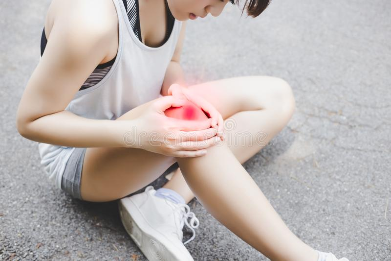 De aantrekkelijke mooie vrouw krijgt ongeval en pijnlijke plekken haar knie De mooie joggervrouw wordt gekwetst of pijnlijk zodat stock afbeelding