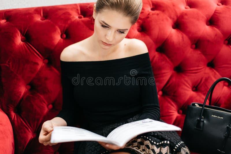 De aantrekkelijke mooie vrouw met natuurlijke samenstelling in zwart overhemd met naakte schouders leest het tijdschrift op het r stock foto