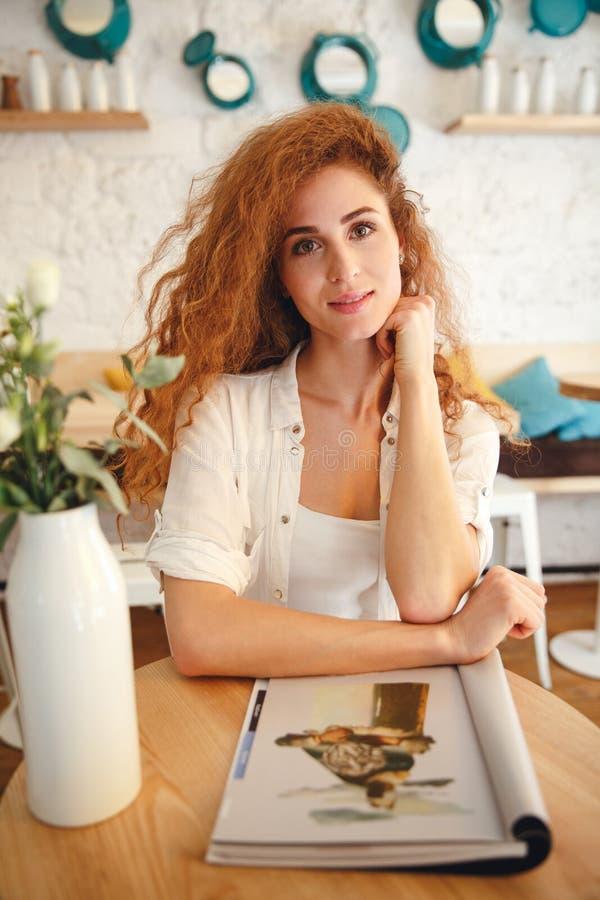 De aantrekkelijke mooie zitting van de roodharige jonge dame in koffie stock afbeelding
