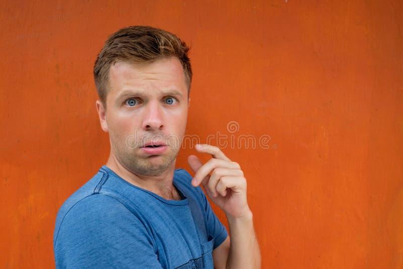 De aantrekkelijke nadenkende jonge mens is verward en onzeker stock foto's