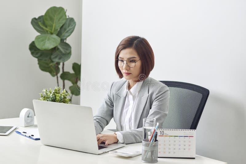 De aantrekkelijke onderneemster zit bij bureau met computer en kalender in het bureau royalty-vrije stock foto's