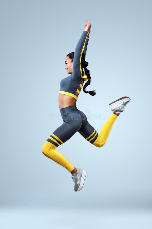 De aantrekkelijke opgewekte danser van het geschiktheidsmeisje in het sportwear die springen van vreugde over grijze achtergrond  stock afbeelding