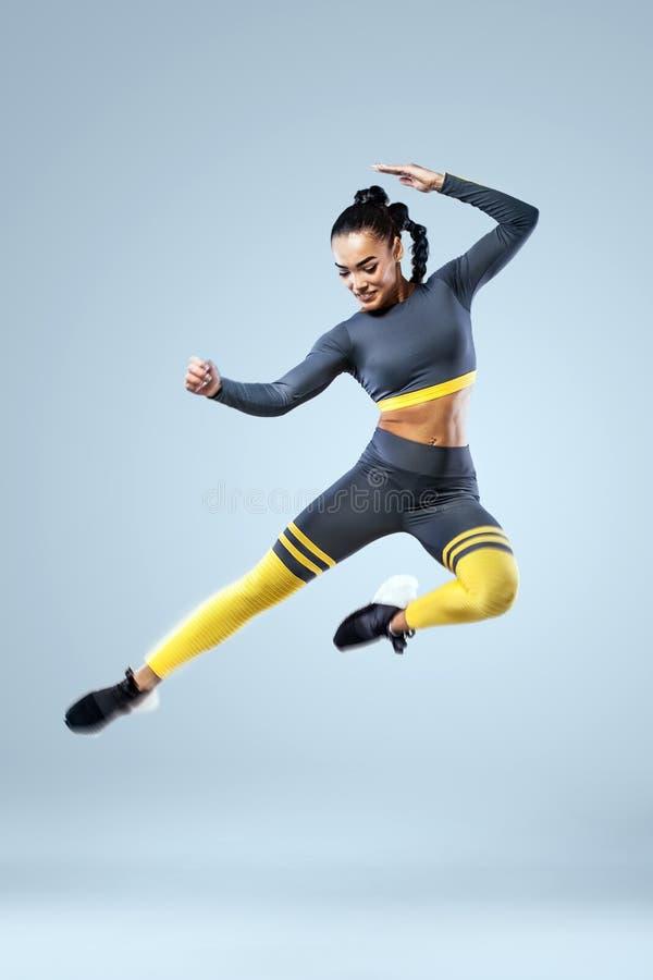 De aantrekkelijke opgewekte danser van het geschiktheidsmeisje in het sportwear die springen van vreugde over grijze achtergrond  stock fotografie