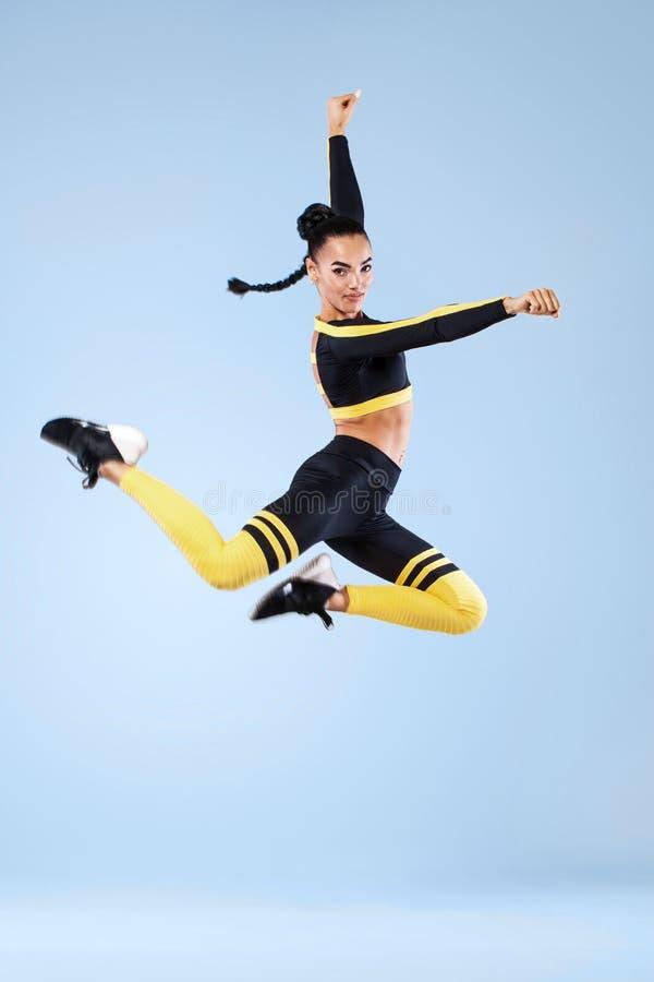 De aantrekkelijke opgewekte danser van het geschiktheidsmeisje in het sportwear die springen van vreugde over grijze achtergrond  stock foto