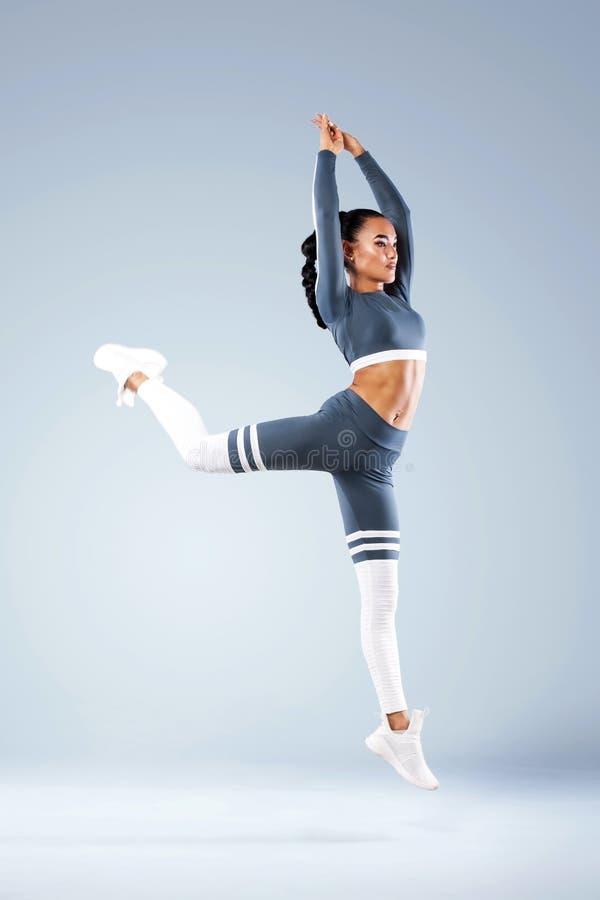 De aantrekkelijke opgewekte danser van het geschiktheidsmeisje in het sportwear die springen van vreugde over grijze achtergrond  royalty-vrije stock foto