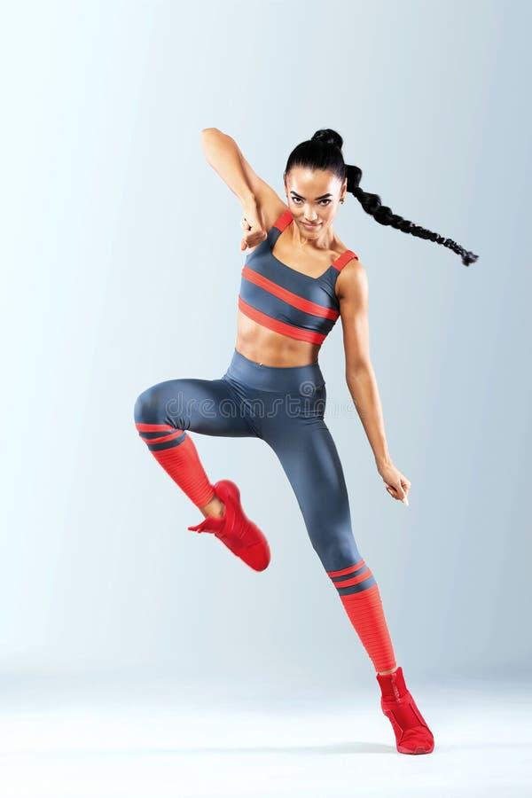 De aantrekkelijke opgewekte die danser van het geschiktheidsmeisje in sportwear over grijze achtergrond wordt geïsoleerd stock foto's