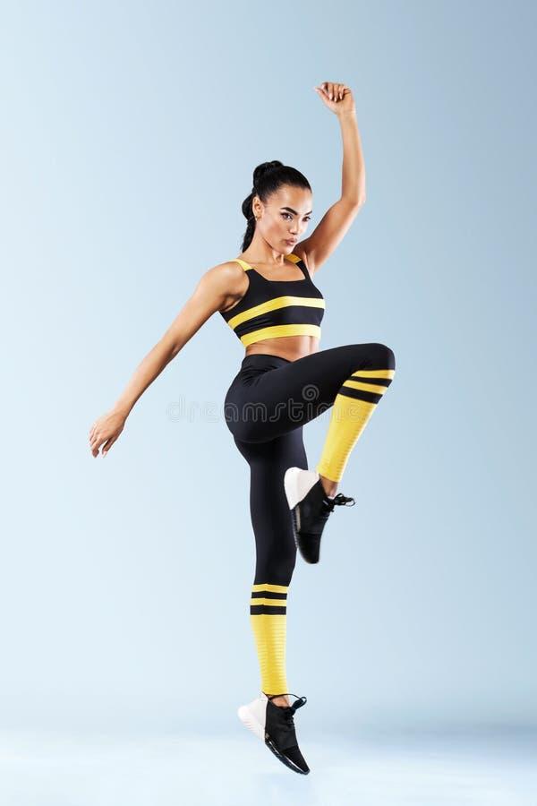 De aantrekkelijke opgewekte die danser van het geschiktheidsmeisje in sportwear over grijze achtergrond wordt geïsoleerd royalty-vrije stock afbeeldingen