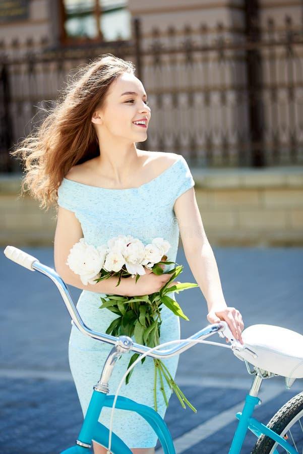 De aantrekkelijke pioenen van de vrouwenholding en het kijken aan de kant terwijl de wind haar haar tijdens hete de zomerdag blaa royalty-vrije stock afbeelding