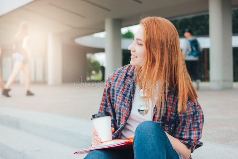 De aantrekkelijke roodharige glimlachende studente kleedde vrijetijdskleding met kop van koffie om in handen op straat in stad te royalty-vrije stock foto's