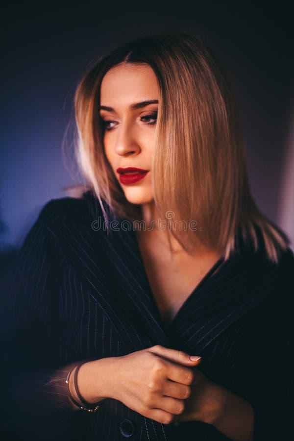De aantrekkelijke sexy blondevrouwen dragen zwart bustehouder en jasje Het gelijk maken maakt omhoog zwarte smokeyogen en rode li stock afbeelding