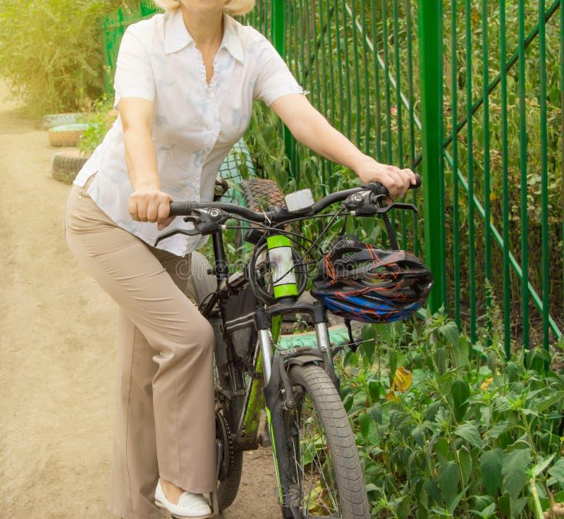 De aantrekkelijke slanke vrouw op middelbare leeftijd in licht broeken en overhemd bevindt zich dichtbij de fiets in het Park op  stock foto