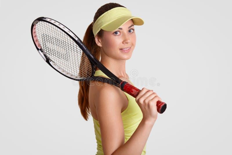 De aantrekkelijke sportieve vrouw met schone huid, draagt toevallige kleding, houdt tennis raquet, heeft poneystaart, die actieve stock afbeeldingen