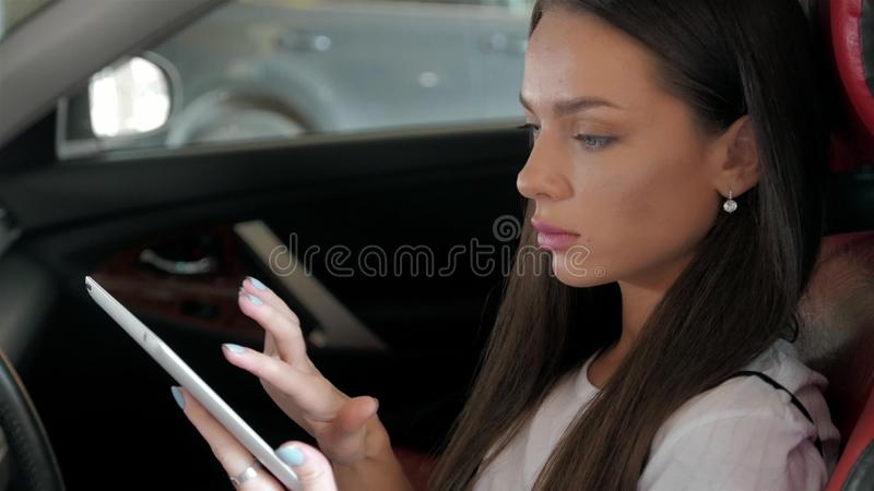 De aantrekkelijke uitvoerende vrouwelijke van de de luxeauto van het managerwerk computer van de de aanrakingstablet stock foto's