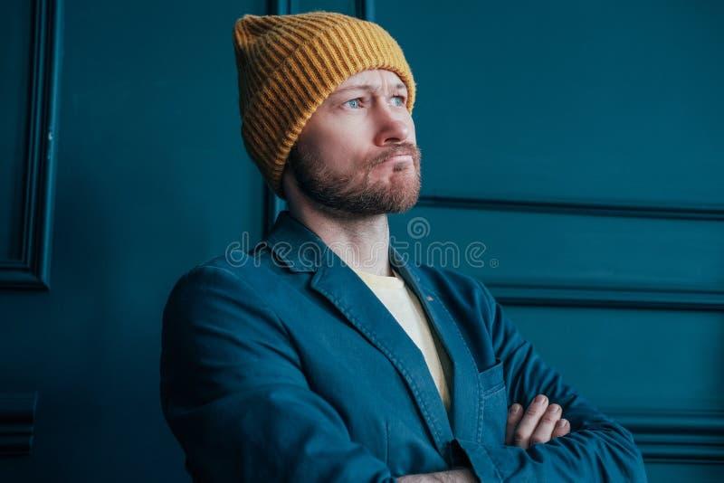De aantrekkelijke volwassen gebaarde boze mens hipster in gele hoed bekijkt camera en doorploegde zijn brows op blauwe muurachter royalty-vrije stock fotografie