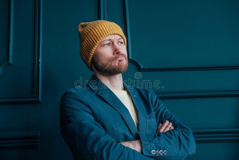 De aantrekkelijke volwassen gebaarde boze mens hipster in gele hoed bekijkt camera en doorploegde zijn brows op blauwe muurachter stock afbeeldingen