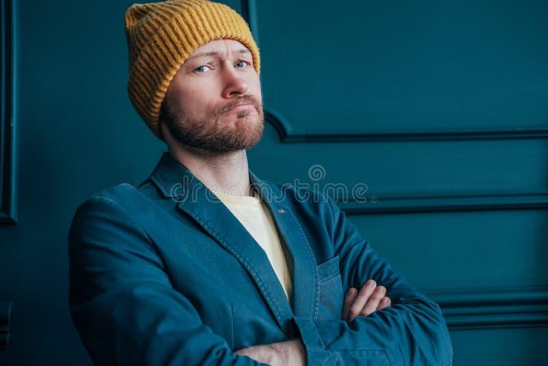 De aantrekkelijke volwassen gebaarde boze mens hipster in gele hoed bekijkt camera en doorploegde zijn brows op blauwe muurachter royalty-vrije stock afbeeldingen