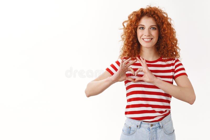 De aantrekkelijke vrolijke blije roodharige krullend-haired vrouwelijke vrijwilliger die de veilige zorg van de dieren het wild u stock afbeelding