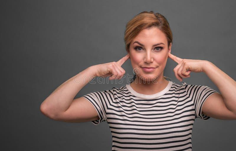 De aantrekkelijke vrouw behandelt haar oren met vingers op een grijze achtergrond royalty-vrije stock foto's
