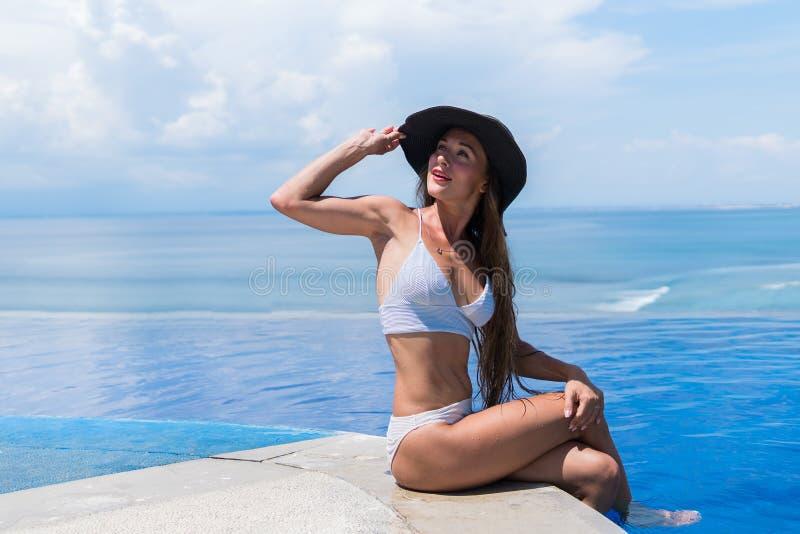 De aantrekkelijke vrouw in bikini en met grijze hoed ontspant in een oneindigheidspool royalty-vrije stock foto