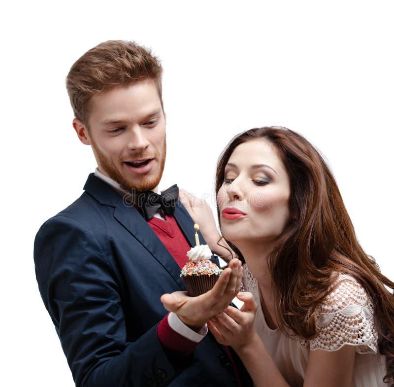 De aantrekkelijke vrouw blaast uit een kaars op cake stock afbeelding