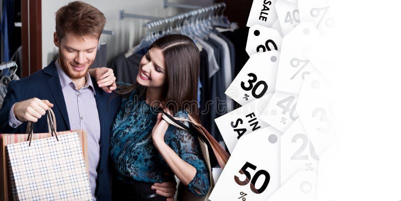 De aantrekkelijke vrouw en de jonge man gaan winkelend bij de opslag stock fotografie
