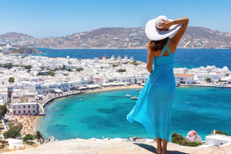 De aantrekkelijke vrouw geniet van de mening over de stad van Mykonos stock afbeeldingen