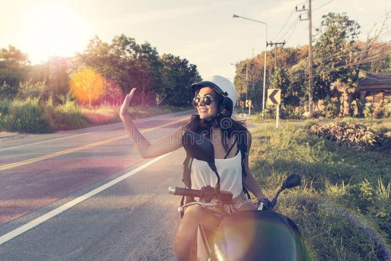De aantrekkelijke Vrouw geniet Zon van Gloed op Motorfietsslijtage Helemt op Reis van de de Vrouwenmotorrijder van de Plattelands stock fotografie