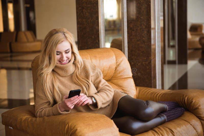 De aantrekkelijke vrouw heeft een koffiepauze die haar mobiele telefoon met behulp van stock afbeeldingen