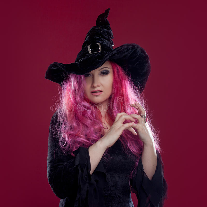 De aantrekkelijke vrouw in heksenhoed en kostuum met rood haar voert magisch op roze achtergrond uit Halloween, verschrikkingsthe royalty-vrije stock foto's