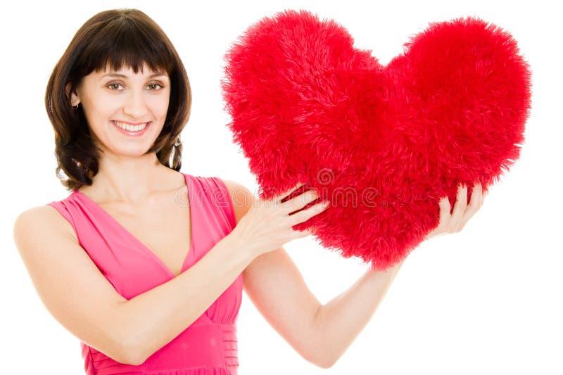 De aantrekkelijke vrouw houdt een hart in zijn handen stock fotografie