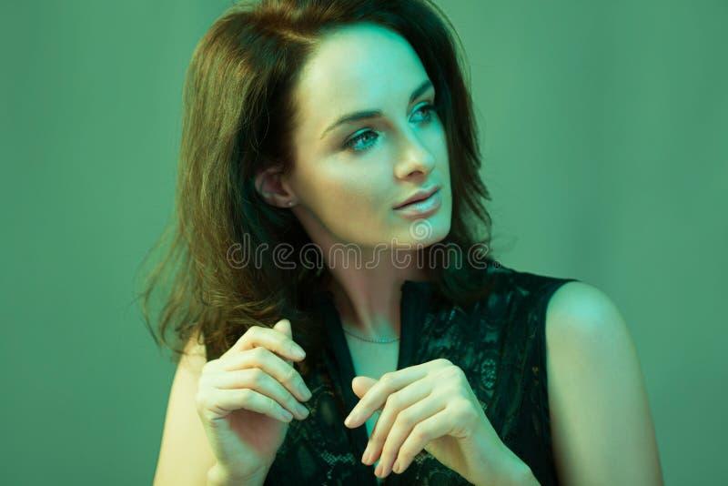 De aantrekkelijke vrouw kleedde zich in manierkleding in de lichten van de neonnacht stock afbeelding