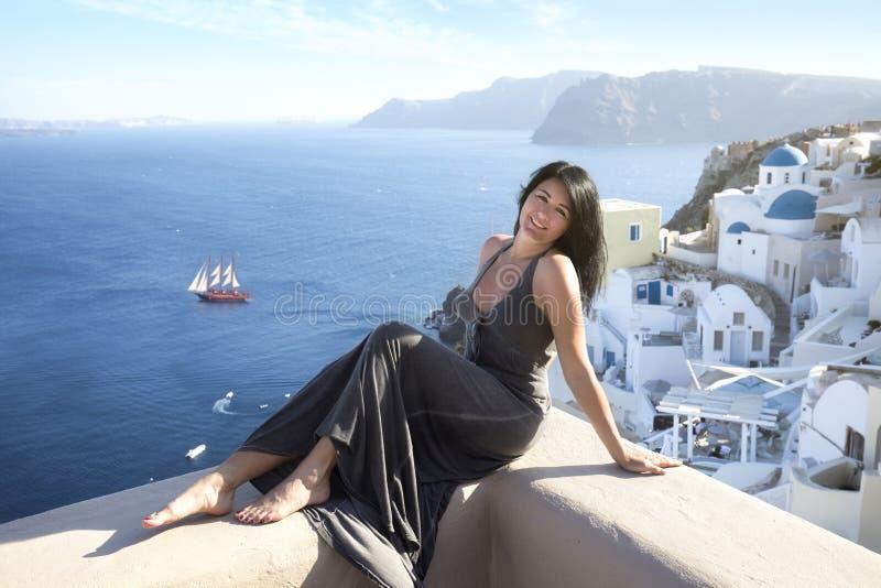De aantrekkelijke vrouw met een lange kleding zit op een muur in Oia, Santorini stock foto's