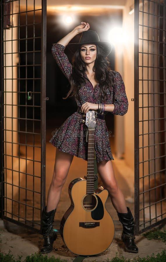 De aantrekkelijke vrouw met land kijkt, de binnen geschotene, Amerikaanse stijl van het land Meisje met zwarte cowboyhoed en gita stock afbeelding