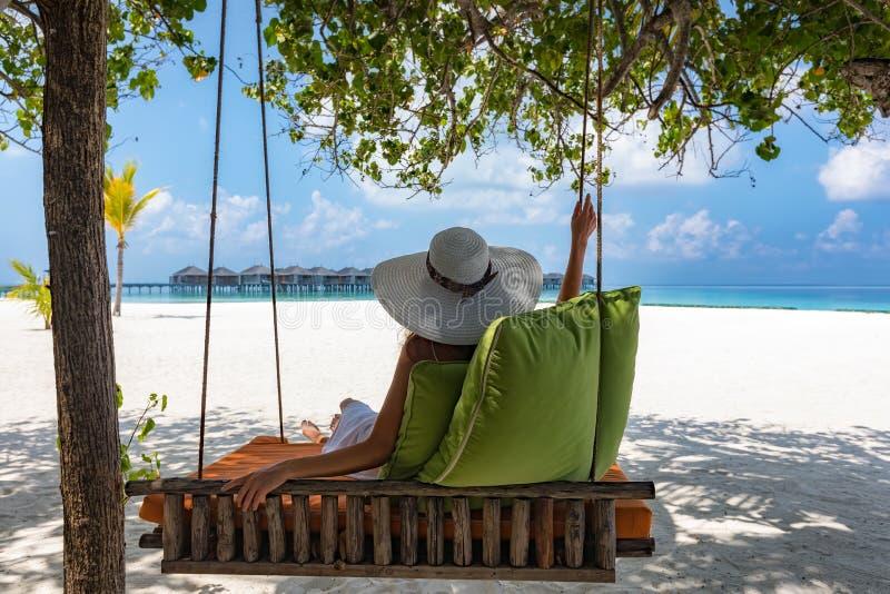 De aantrekkelijke vrouw ontspant bij een tropisch strand stock afbeelding