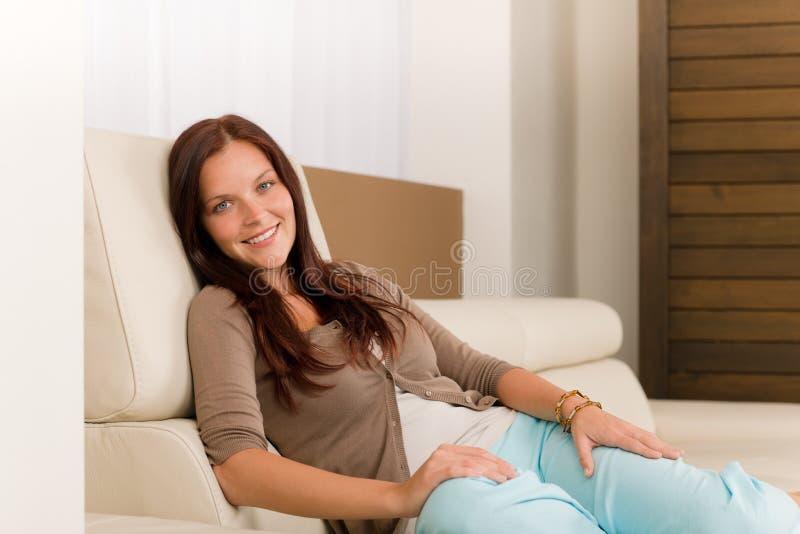De aantrekkelijke vrouw ontspant de bank van het woonkamerleer stock afbeelding